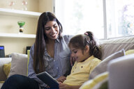 Happy mother and daughter sitting on couch at home using tablet - ABZF02233