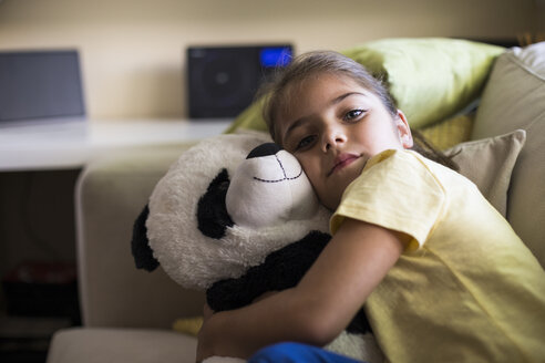Little girl lying on couch at home cuddling with teddy panda bear - ABZF02239