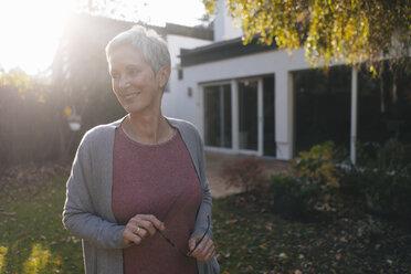 Smiling mature woman standing in garden - KNSF05502