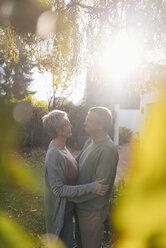 Affectionate senior couple embracing in garden - KNSF05508