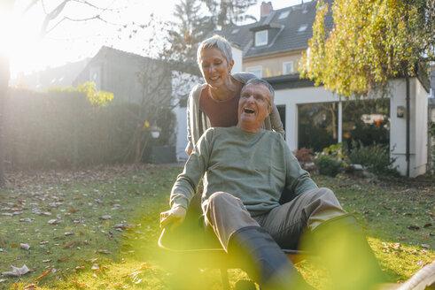 Happy senior couple having fun with wheelbarrow in garden - KNSF05514