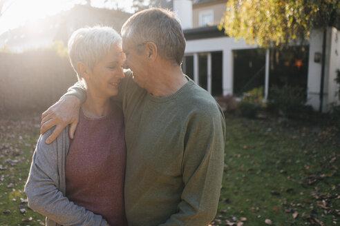 Affectionate senior couple embracing in garden - KNSF05517