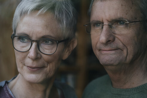 Confident senior couple looking out of window - KNSF05523