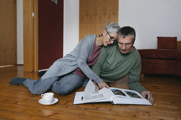 Senior couple sitting on the floor at home looking at photo album - KNSF05532