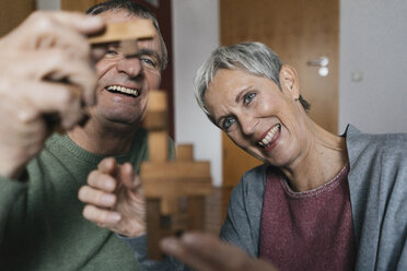 Happy senior couple playing dexterity game at home - KNSF05544
