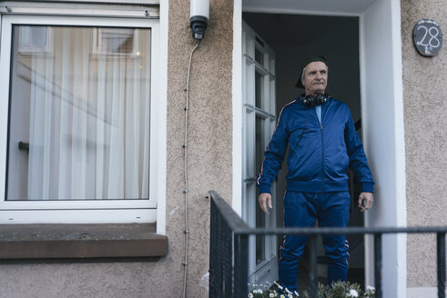 Sportive senior man in tracksuit staning in house entrance - KNSF05550
