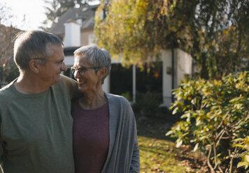 Affectionate senior couple embracing in garden - KNSF05556