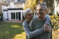 Happy affectionate senior couple hugging in garden - KNSF05562