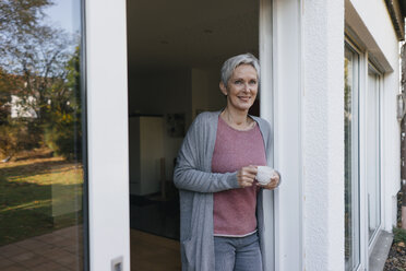 Smiling mature woman with cup of coffee at terrace door - KNSF05565