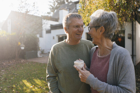 Happy senior couple with cup of coffee in garden - KNSF05568