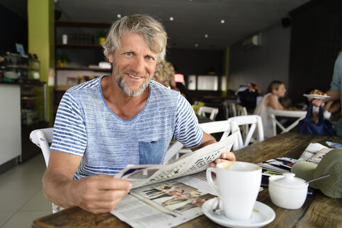 Portrait of smiling mature man sitting in a coffee shop reading newspaper - ECPF00516