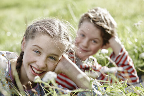 Portrait of smiling girl lying on a meadow with little brother at the background - RORF01743
