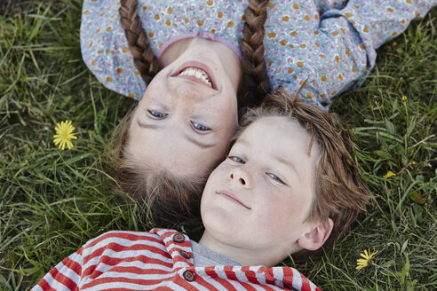 Portrait of girl and and her little brother lying head to head on a meadow - RORF01749