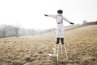 six year old cool boy wearing white space suit ist posing outdoor in a meadow, sometimes with virtual reality glasses - HMEF00203