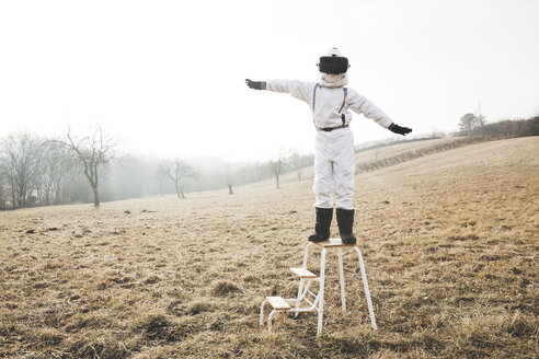 Boy wearing white space suit with raised arms on a step with virtual reality glasses - HMEF00203