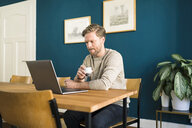 Man working on laptop on wooden table in home office drinking espresso - SBOF01728