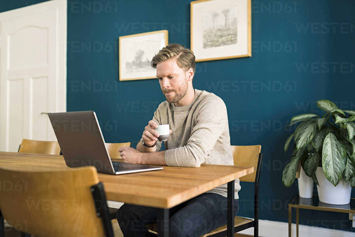 Man working on laptop on wooden table in home office drinking espresso - SBOF01728 - Steve Brookland/Westend61