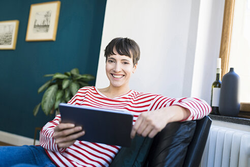 Portrait of happy short-haired woman in lounge chair holding tablet - SBOF01731