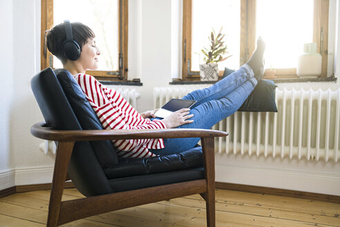 Short-haired woman with headphones relaxing in lounge chair in stylish apartment - SBOF01734