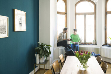 Casual couple having a conversation and sitting at window in stylish apartment - SBOF01740