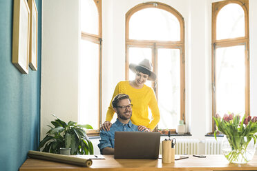 Casual entrepreneur couple in home office working at laptop and smiling - SBOF01752