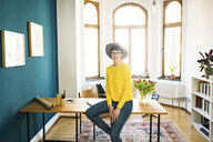Portrait of smiling businesswoman in home office sitting on table - SBOF01761