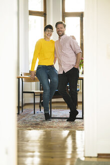 Portrait of happy couple at table in stylish apartment - SBOF01764