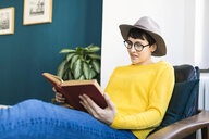 Woman relaxing in lounge chair reading a book - SBOF01767