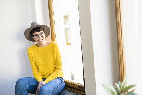 Happy woman sitting on windowsill looking outside - SBOF01770