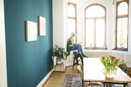 Woman sitting on windowsill in stylish apartment holding coffee mug and reading a book - SBOF01773