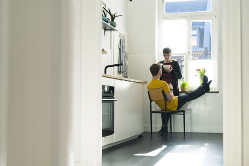 Couple at the window in kitchen at home - SBOF01779
