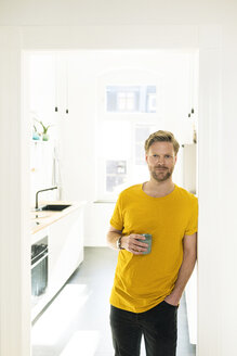 Confident casual man with coffee mug leaning against door case - SBOF01785