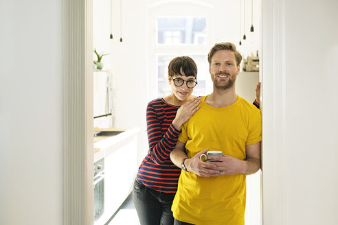 Happy couple leaning in door case in front of their kitchen - SBOF01788