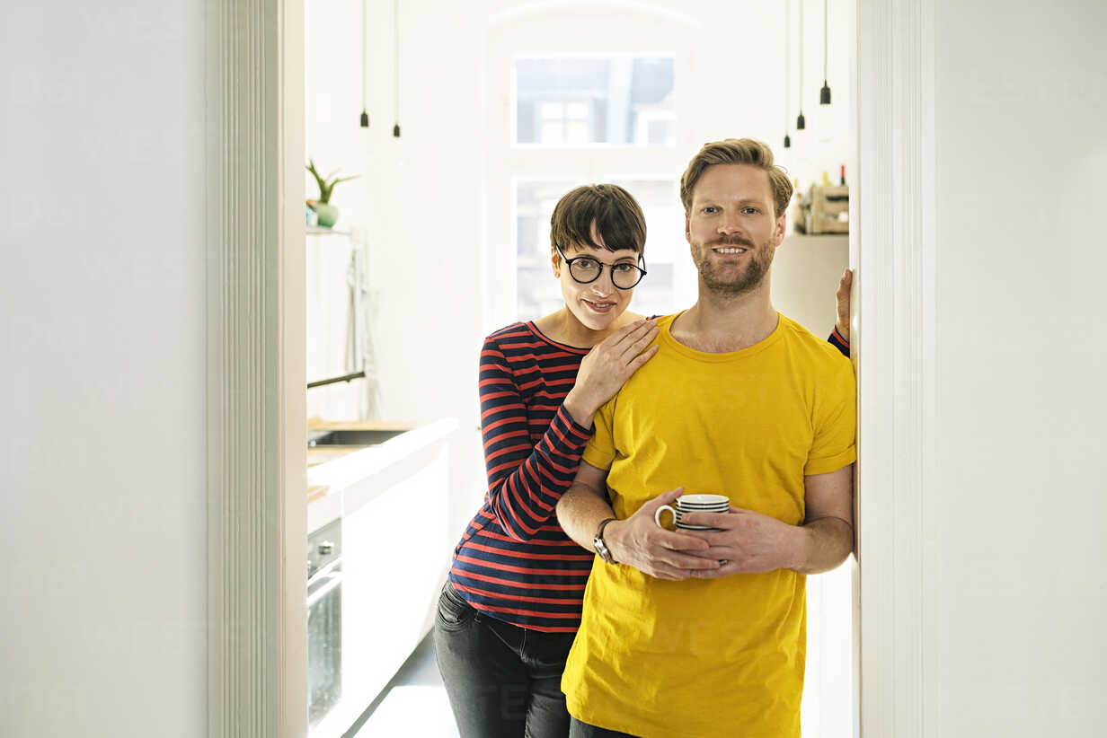 Happy couple leaning in door case in front of their kitchen - SBOF01788 - Steve Brookland/Westend61