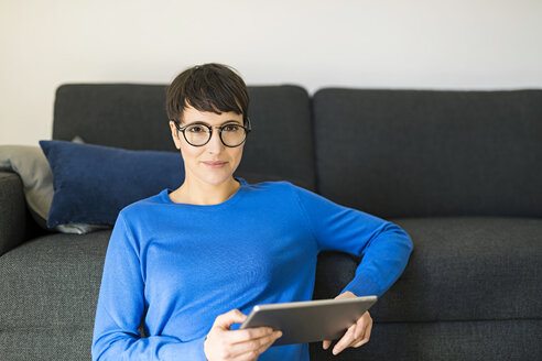 Portrait of casual short-haired woman in living room using a tablet - SBOF01794
