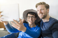 Happy casual couple taking a selfie with tablet in living room - SBOF01797