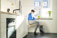 Short-haired woman sitting on bench in kitchen at the window using smartphone - SBOF01803