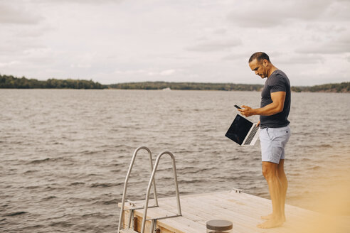 Full length of man with laptop using phone while standing on jetty against sky - MASF11123