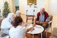 Senior friends playing cards at table in nursing home - MASF11132