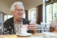Senior man using mobile phone at breakfast table in nursing home - MASF11147