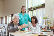Smiling healthcare worker and senior woman listening to man during breakfast at home - MASF11153