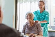Smiling female caretaker massaging shoulders of senior woman at home - MASF11159
