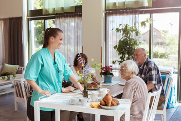 Female caregiver serving meal to senior people in nursing home - MASF11162