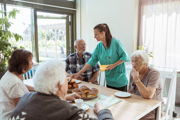 Elderly care nurse serving meal to people at table in nursing home - MASF11165