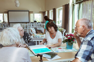 Senior friends looking at photograph in book at nursing home - MASF11171