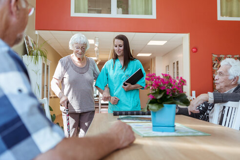 Senior woman and nurse walking arm in arm towards friends at nursing home - MASF11174