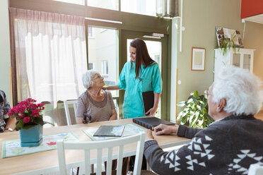 Young nurse talking with senior woman sitting at table in nursing home - MASF11177