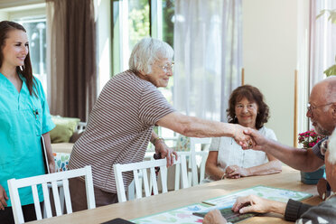 Nurse looking at senior woman greeting friends at nursing home - MASF11180