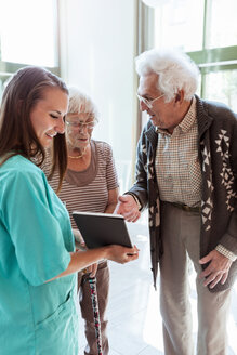Young female nurse showing digital tablet to senior couple at nursing home - MASF11183