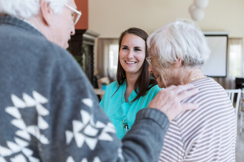 Smiling young female nurse looking at senior couple in nursing home - MASF11186